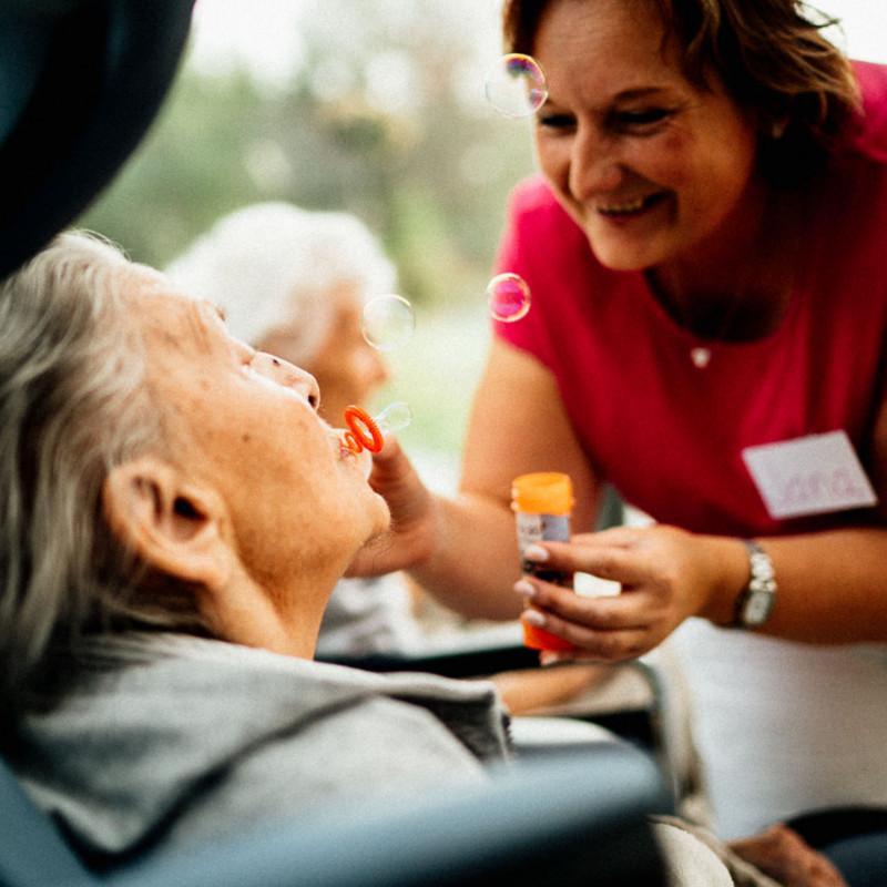 Seniorka s pečovatelkou foukají bubliny z bublifuku